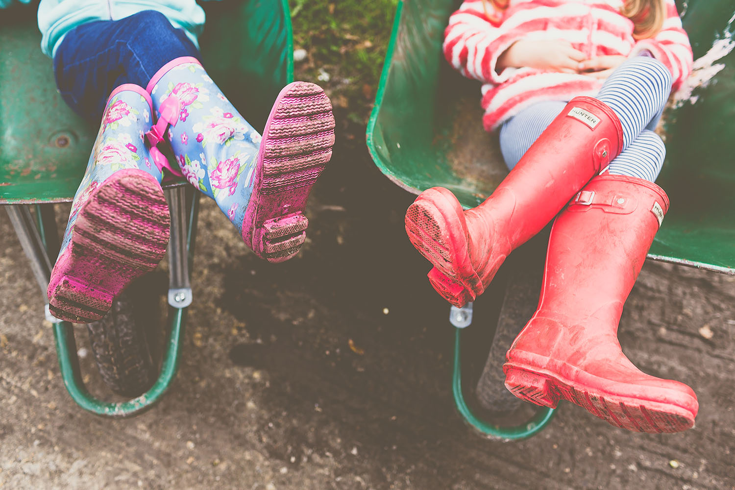 Children sitting in a wheel barrow with wellies on