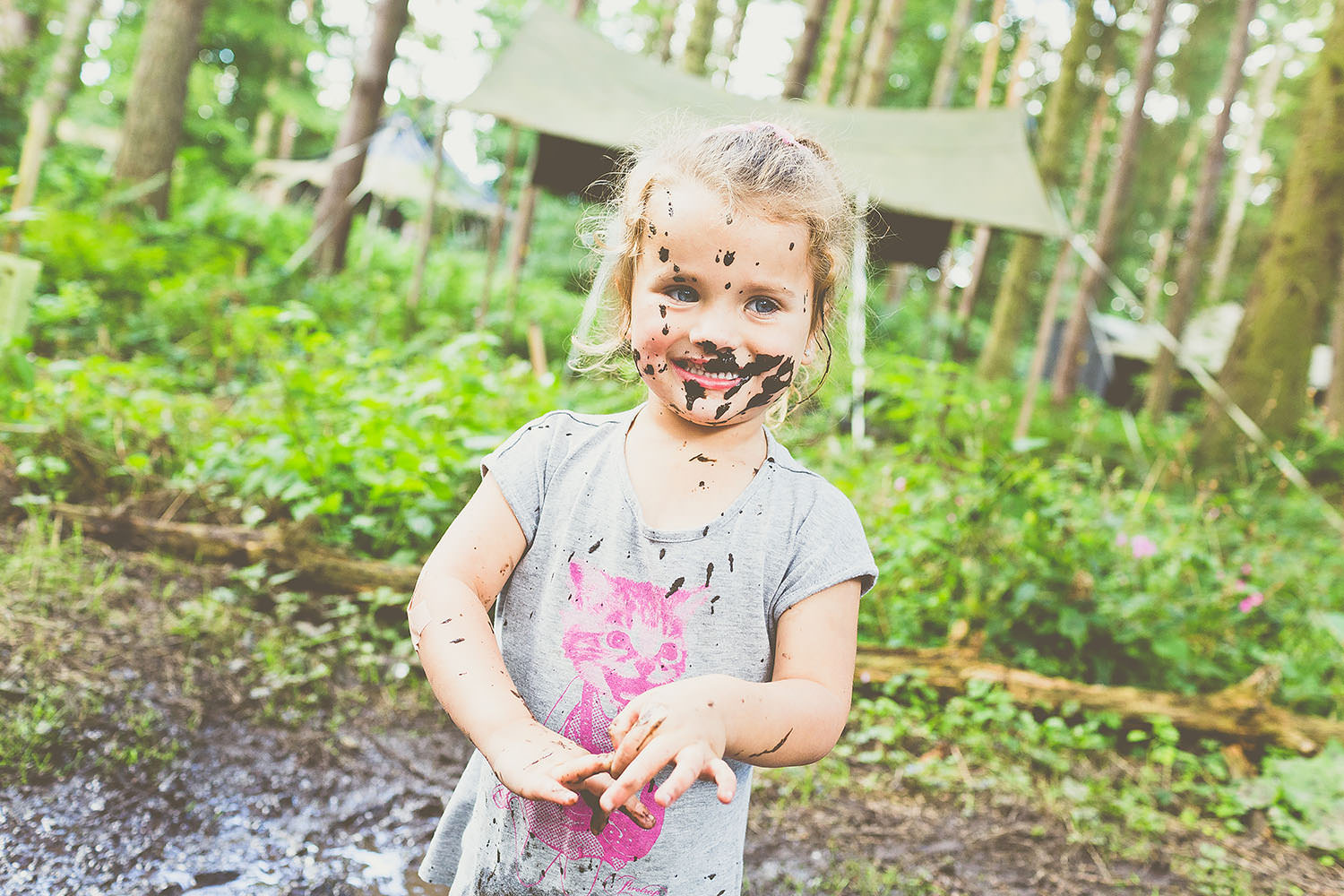 A small child with mud on her face.