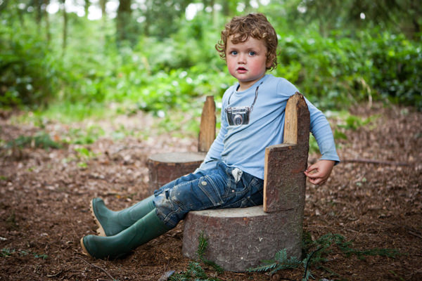 Child sitting on a wooden log