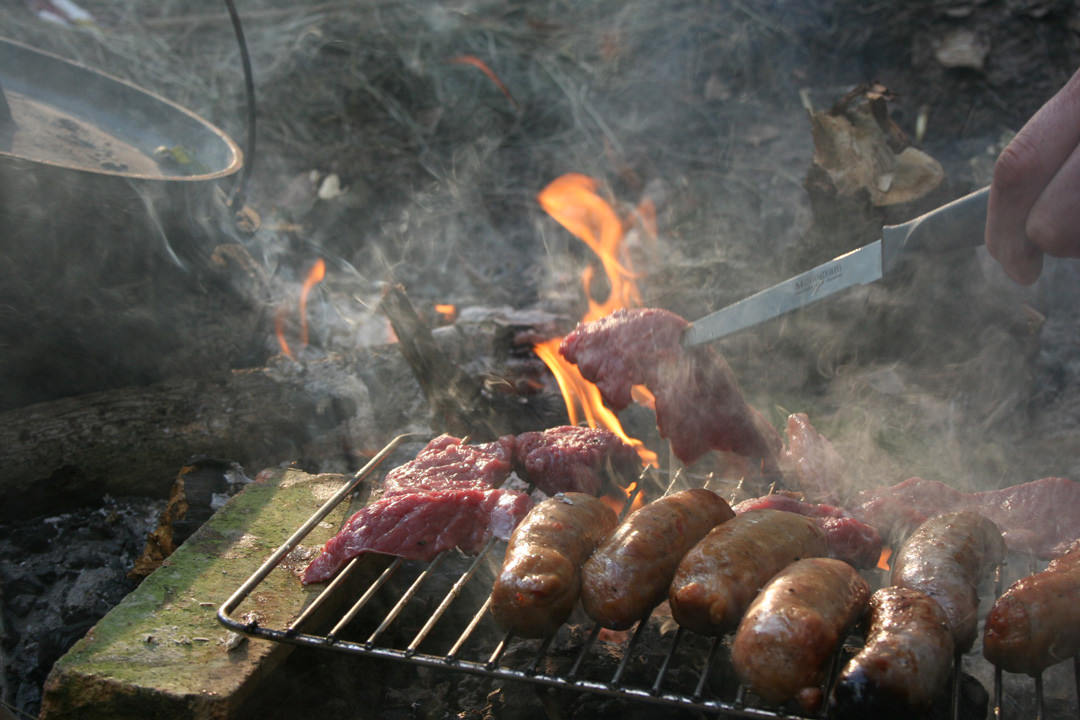 Cooking meat and sausages on a barbeque