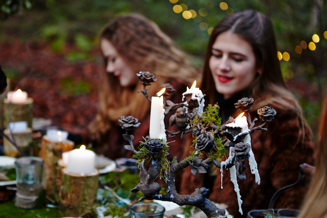 Two people sat at a picnic bench decorated with candles and foliage