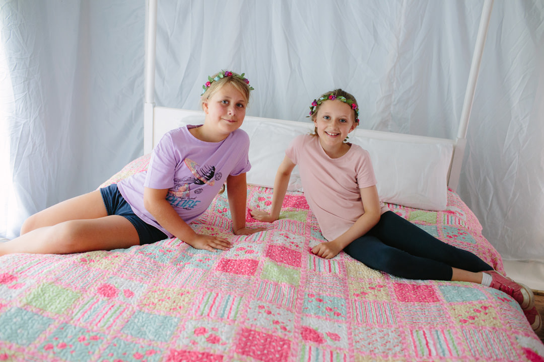 Two children sitting on a colourful bed