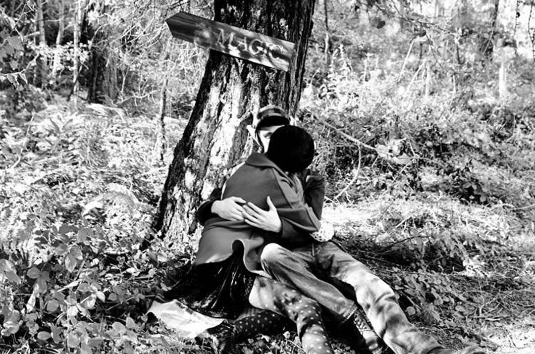 Two people kissing in woodland