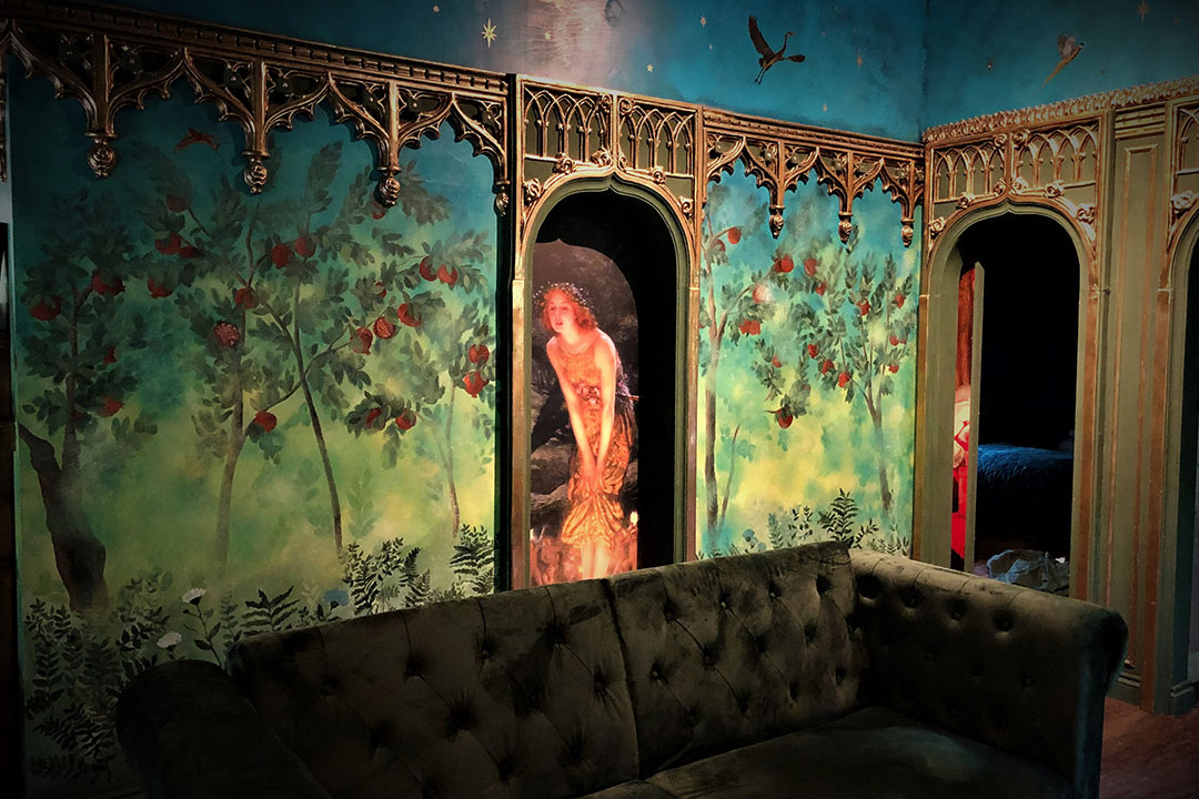 A bath and shower surrounded by a curtain in a wooden building