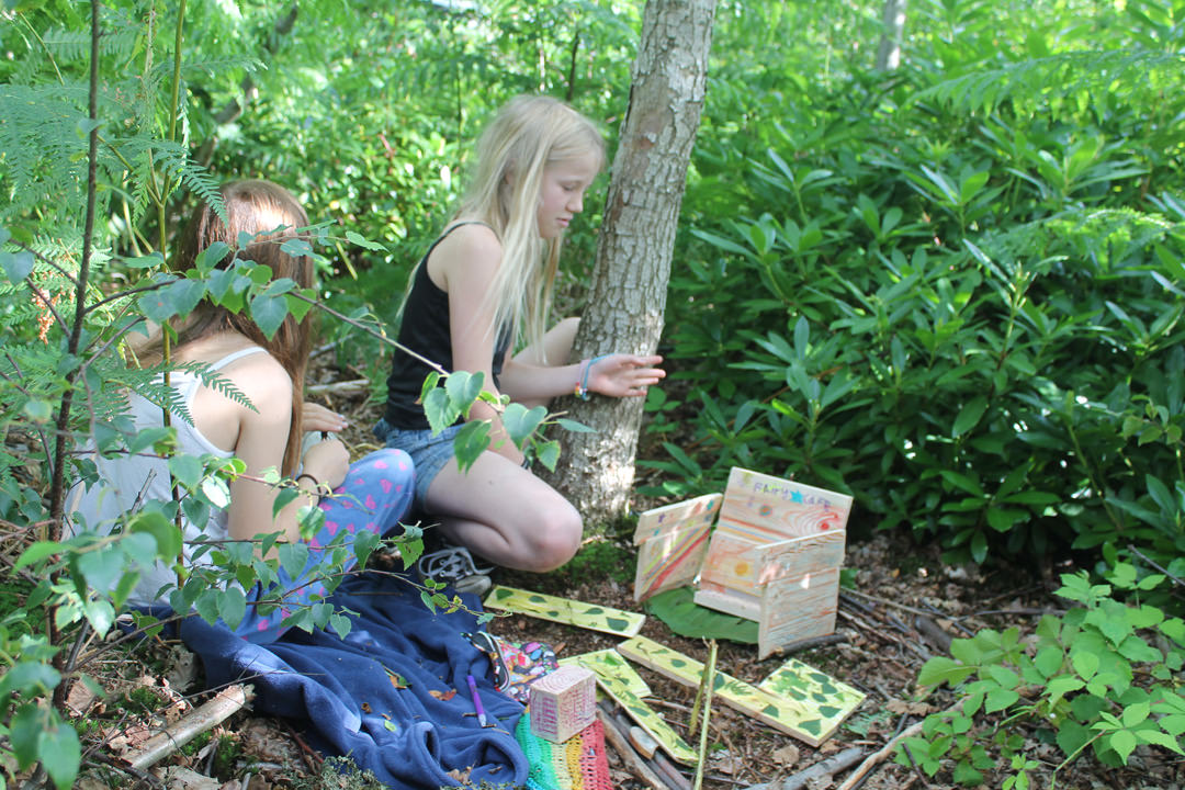 Children playing with wooden toys in a small woodland clearing
